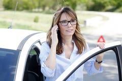 Женщина звоня аварийный вызов на дороге Стоковые Фото