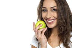 Женщина здоровья сознательная около для еды свежего зеленого яблока Стоковые Изображения RF