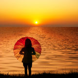 женщина зонтика захода солнца силуэта озера Стоковые Фотографии RF
