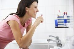 женщина зубов ванной комнаты чистя щеткой Стоковое Фото