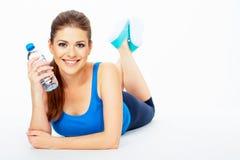 Женщина зубов усмехаясь лежа на поле с botle воды Стоковые Изображения RF