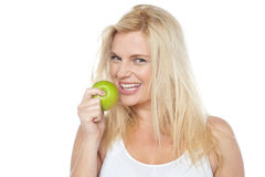 Женщина здоровья сознательная около для того чтобы принять укус от зеленого яблока Стоковые Фото