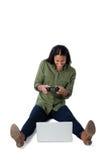 Женщина играя видеоигру на компьтер-книжке против белой предпосылки Стоковая Фотография