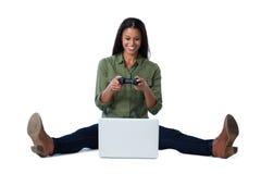 Женщина играя видеоигру на компьтер-книжке против белой предпосылки Стоковое фото RF