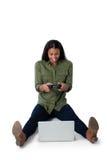 Женщина играя видеоигру на компьтер-книжке против белой предпосылки Стоковые Изображения