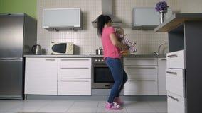 Женщина играя и танцуя с сыном младенца в кухне акции видеоматериалы