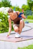 Женщина играя миниатюрный гольф стоковые фото