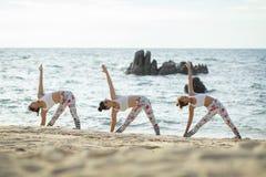 Женщина 3 играя представление йоги на пляж моря Стоковая Фотография