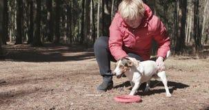 Женщина играя с ее собакой на внешнем парке сток-видео
