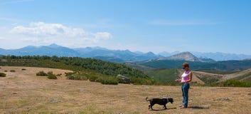 Женщина играя с ее собакой поверх горы Palentina Испания панорамно стоковые изображения