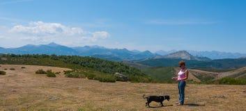 Женщина играя с ее собакой поверх горы Palentina Испания панорамно стоковое изображение rf