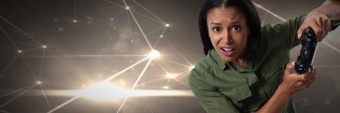 женщина играя с регулятором компютерной игры с светлыми соединениями на предпосылке зеленых холмов Стоковые Фото