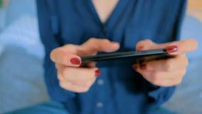 Женщина играя с умным телефоном видеоматериал