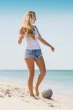 Женщина играя футбол на пляже стоковое изображение