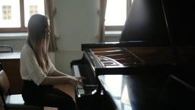 Женщина играя черный рояль на предпосылке окна в замедленном движении сток-видео
