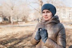 Женщина идет в парк осени Я клал руки о груди стоковая фотография