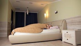 Женщина идет положить в постель Она лежит на кровати, в спальне и перед идти положить она в постель использует телефон 2th confus сток-видео