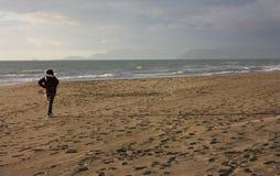 Женщина идет спокойное и ослабленная на зимний день он принимает перерыв на море, дыша соль и опорожнять его разум идя на s стоковые изображения rf