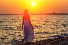 Женщина идя вдоль пляжа на часах захода солнца или восхода солнца остатков стоковые фото