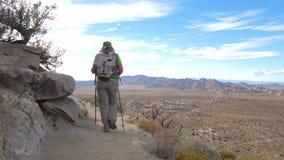 Женщина идя вдоль пути горы вдоль скалы с помощью Trekking ручке акции видеоматериалы