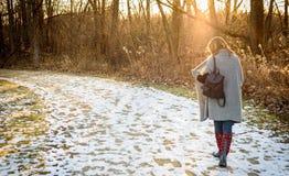 Женщина идя в древесины в зиме на заходе солнца Стоковая Фотография RF