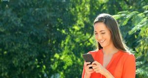 Женщина идя используя умный телефон в парке
