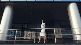 Женщина идя и говоря на мобильном телефоне в городе около здания scyscraper в замедленном движении видеоматериал