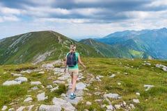 Женщина идя на горную тропу стоковое изображение