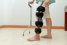 Женщина идя на костыли, нося поддержка колена стоковое фото rf