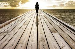 Женщина идя на мост к океану стоковое фото