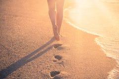 Женщина идя на песчаный пляж выходя следы ноги в песок на s Стоковое Фото