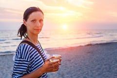 Женщина идя на пляж в прибое на заходе солнца стоковые изображения rf