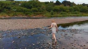 Женщина идя около берега реки сток-видео