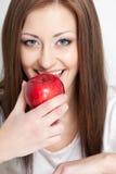 Женщина идя съесть красное яблоко Стоковые Фотографии RF