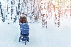 Женщина идя с прогулочной коляской в лесе на зиме Стоковое фото RF