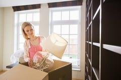 Женщина извлекая лампу от картонной коробки на новом доме Стоковые Фотографии RF