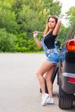 Женщина изменяет колесо автомобиля на дороге Стоковое фото RF