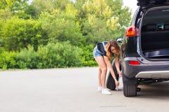 Женщина изменяет колесо автомобиля на дороге Стоковые Фотографии RF