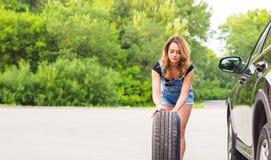 Женщина изменяет колесо автомобиля на дороге Стоковая Фотография