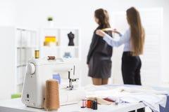 Женщина измеряет ее клиента на магазине портноя Стоковое Изображение RF