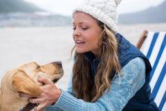 Женщина изнеживая собаку пока сидящ на стуле стоковые фото