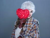 Женщина изолированная на голубой предпосылке смотря вне от красного сердца Стоковое Фото