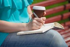Женщина изучая и писать в парке Стоковое Изображение