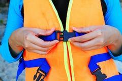 Женщина или маленькая девочка нося оранжевые спасательный жилет или спасательный жилет стоковое фото rf