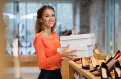 Женщина или продавец с коробками ботинка на магазине Стоковые Изображения