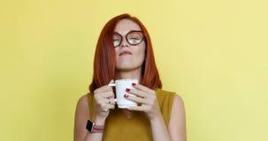 Женщина имбиря в стеклах принимая глоточек кофе акции видеоматериалы