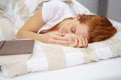 Женщина имбиря спать с книгой в кровати стоковое фото