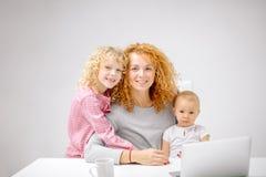 Женщина имбиря с длинным вьющиеся волосы и ее прекрасными маленькими белокурыми детьми стоковые изображения