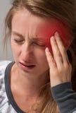 Женщина имеет мигрень головной боли Стоковая Фотография