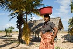 Женщина имеет различные товары в шаре и носит ее на ее голове традиционно Стоковое Изображение RF